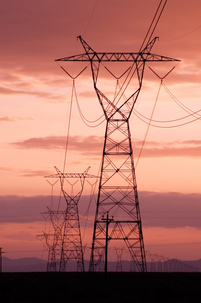 A photo of transmission lines during a beautiful purple and salmon-colored sunset.
